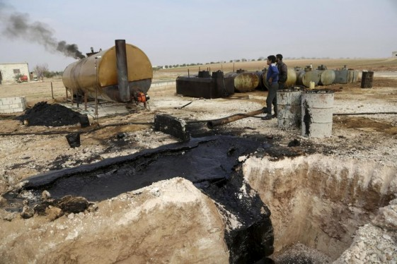 Men work at a makeshift oil refinery site in Marchmarin town, southern countryside of Idlib, Syria in this December 16, 2015, file photo. REUTERS/Khalil Ashawi