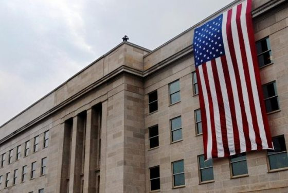 An American flag hangs over the point of impact of the Sept. 11, 2001, attack on the Pentagon for a wreath laying observance of the attacks, near Washington, September 11, 2007.  REUTERS/Jonathan Ernst